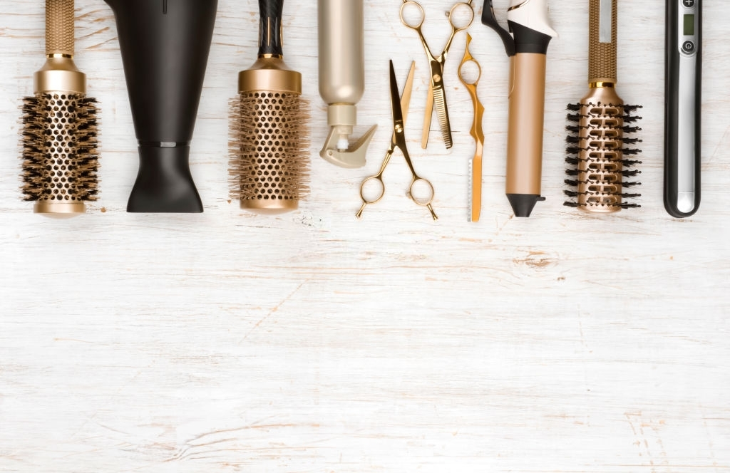 Professional hair dresser tools on wooden background with copy space
